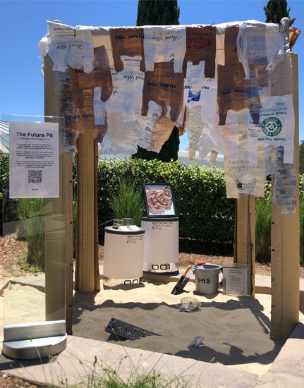 Sand pit transformed into a futuristic archaeological dig with plastic bags and other plastic items in it