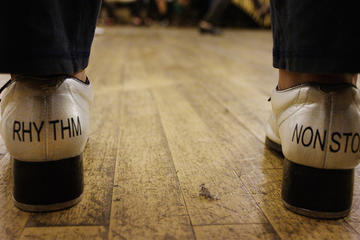 "Tap shoes with the words ""rhythm"" and ""nonstop"" printed on them"