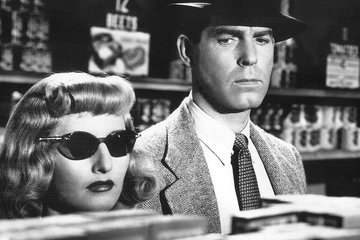 "Black-and-white still from ""Double Indemnity"" of Barbara Stanwyck and Fred MacMurray looking serious in a store."
