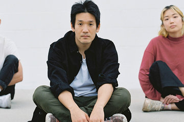 Three musicians sitting on the floor cross-legged in a triangle