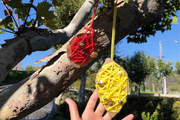 Two fruit cutouts with yarn strung around them hanging from a tree outdoors