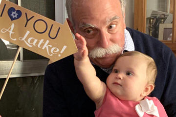 Grandfather with child celebrating hanukkah