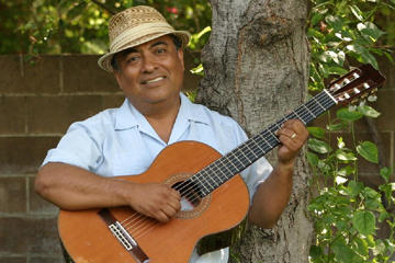 man wearing a hat and holding a guitar in front of a tree
