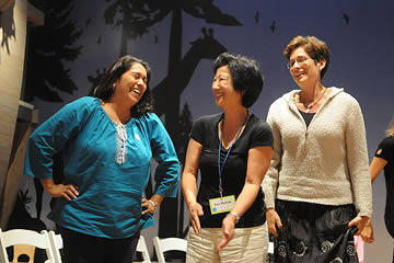 Three women talking and laughing with Noah's Ark exhibit in the background