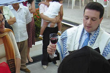 A rabbi holding up a wine glass surrounded by other people at a ceremony