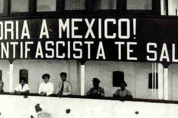 People on a ship with a large sign above them reading ¡Gloria a Mexico!