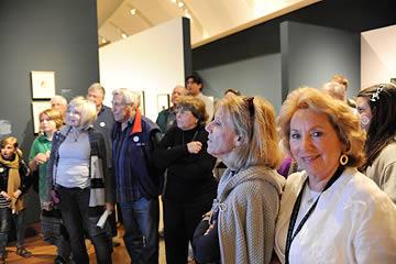 Group of men, women and children standing listening a talk in an exhibit gallery