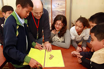 Students and a docent inspecting a pottery sherd