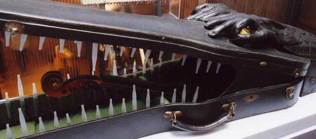 An alligator made out of a violin case and violin parts