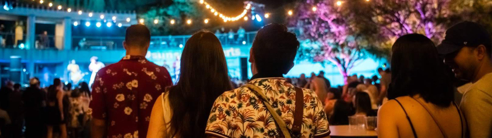 Visitors outdoors under strings of lights looking at stage during Sunset Concerts