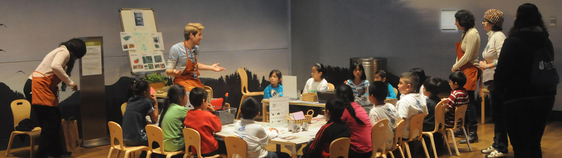 Instructor talking to young children seated around a u-shaped table