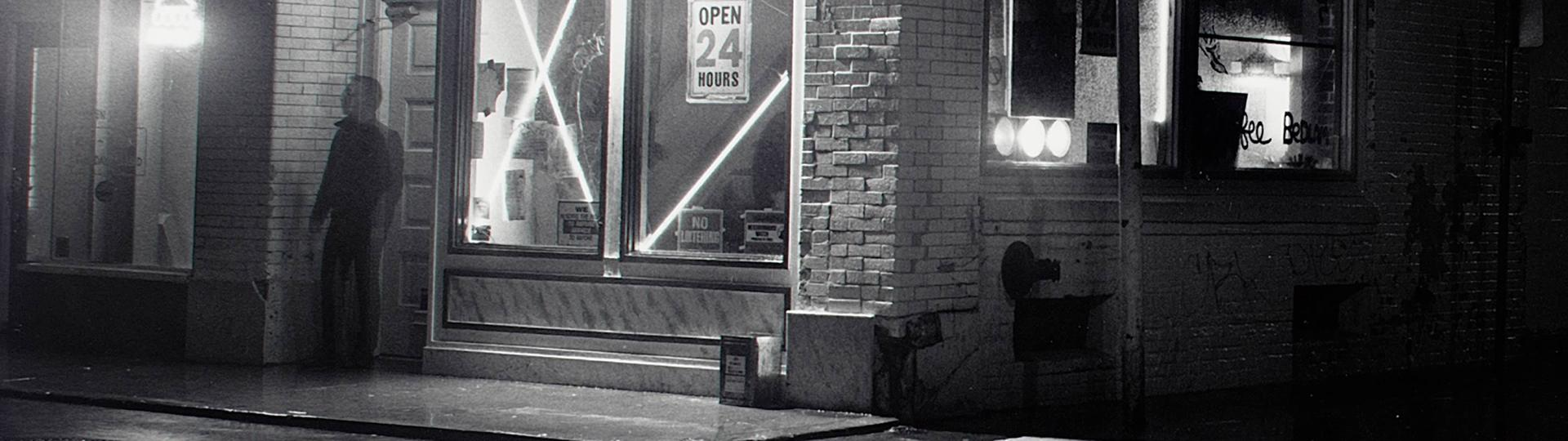 Black and white photo of shadowy man standing outside the doorway of a store at night