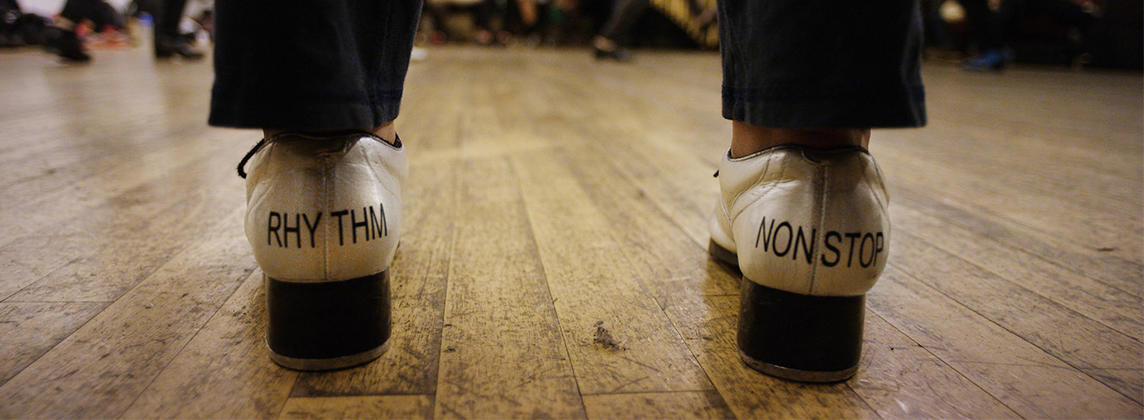 """Tap shoes with the words """"rhythm"""" and """"nonstop"""" printed on them"""