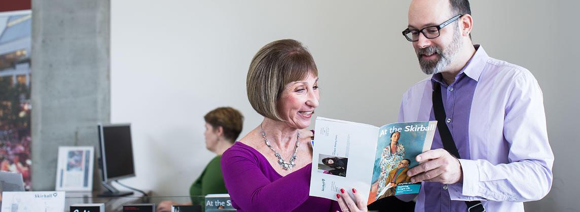 Man and woman looking at Skirball brochure