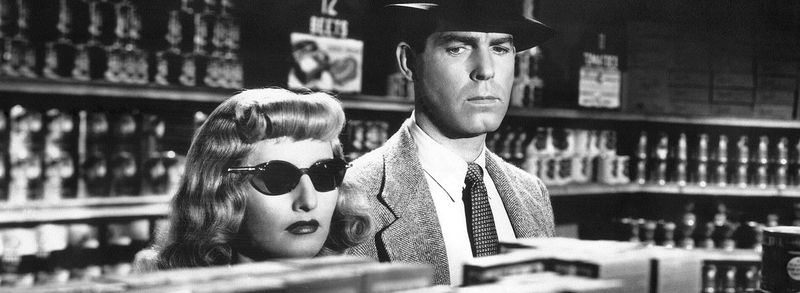 """Black-and-white still from """"Double Indemnity"""" of Barbara Stanwyck and Fred MacMurray looking serious in a store."""