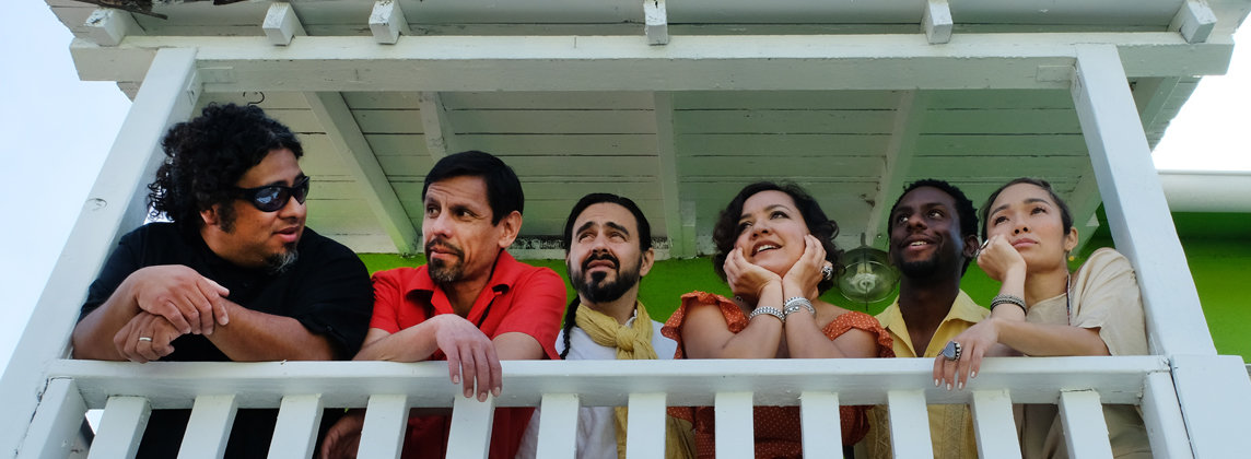 Six musicians smiling while looking over balcony railing