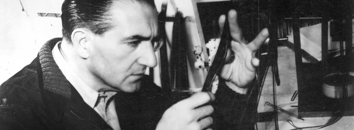 Black and white close-up of Director Fritz Lang inspecting a strip of film