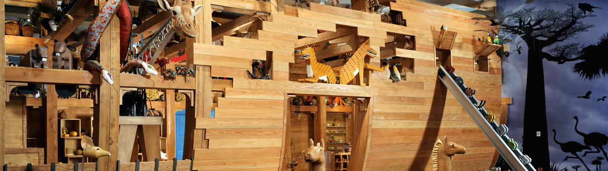 View of Noah's Ark with animals sticking their heads out from the ark and other animals going up a conveyor belt to the ark