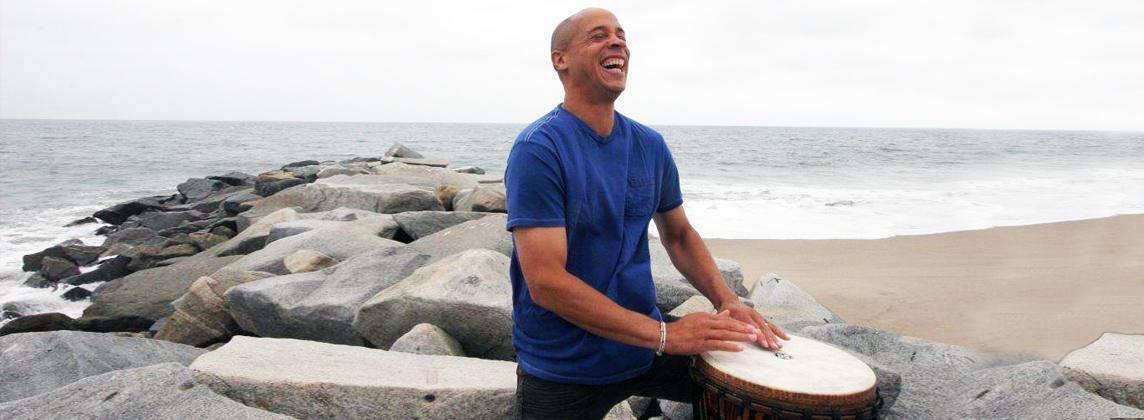 smiling man playing a drum