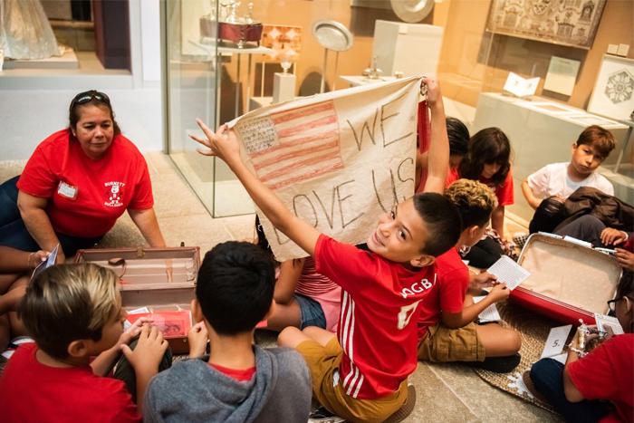 "Student holds up a ""We Love USA"" banner from a suitcase during the Grade 5 Americans and Their Family Stories school tour"