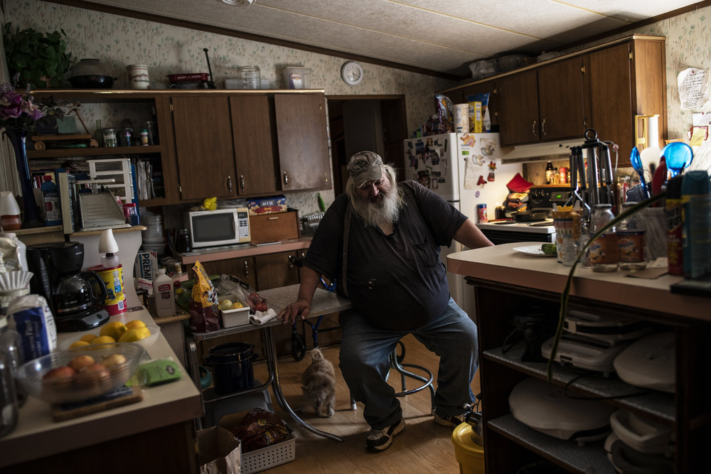 A light skinned adult man with a long grey beard is pictured in his kitchen sitting on a stool.