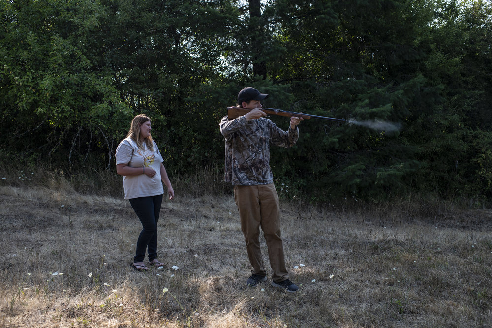 An adult man with light skin tone stands in a field with a gun practicing target shooting. Smoke rises from the gun's barrel and a blond woman with light skin tone looks on smiling.