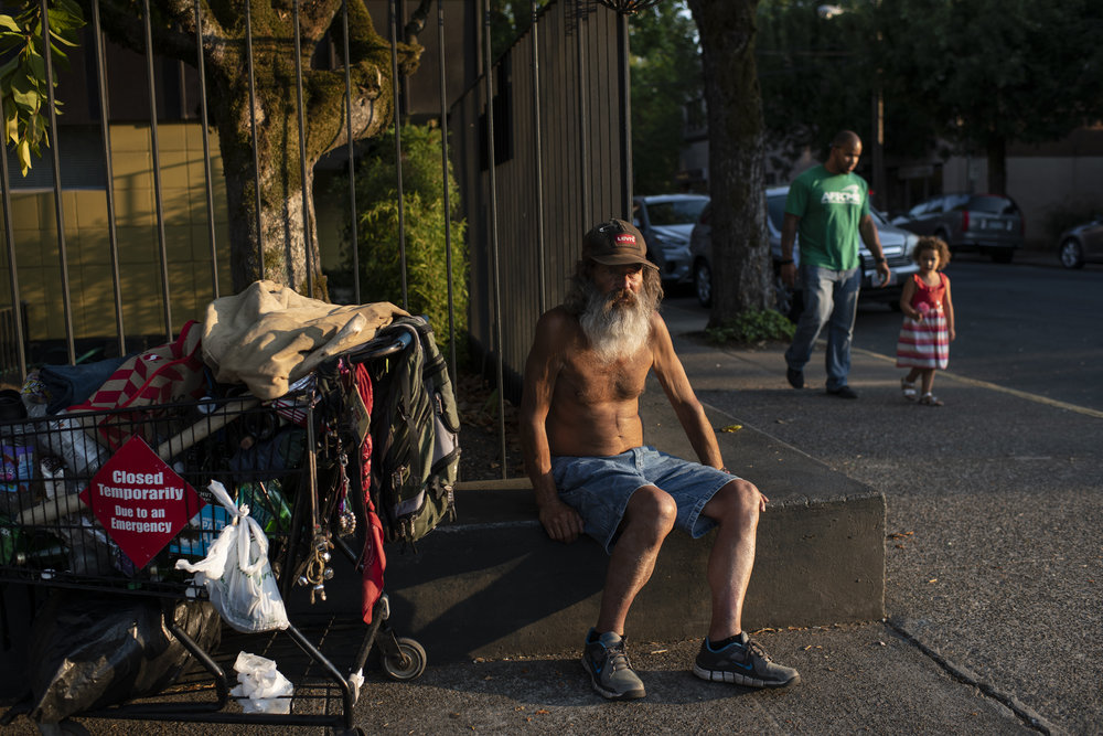 A shirtless adult man with light skin tone sits on the curb next to a shopping cart containing all of his belongings.