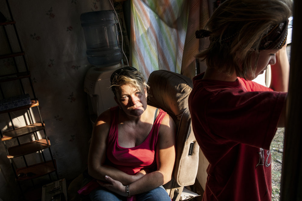 An adult woman with light skin tone is pictured inside a dark room sitting on a recliner. Her tween son with light skin tone peers out a window, pushing back a curtain, causing sunlight to break the darkness and splash across her face.