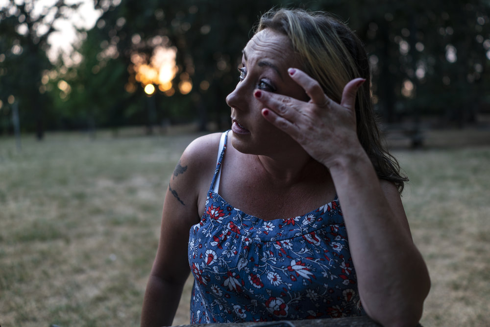 An adult woman with light skin tone is pictured at twilight sitting in a park wiping a tear from her eye.
