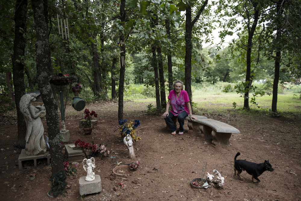 A light skinned older person sits outdoors on a stone bench surrounded by the graves of her dead children.