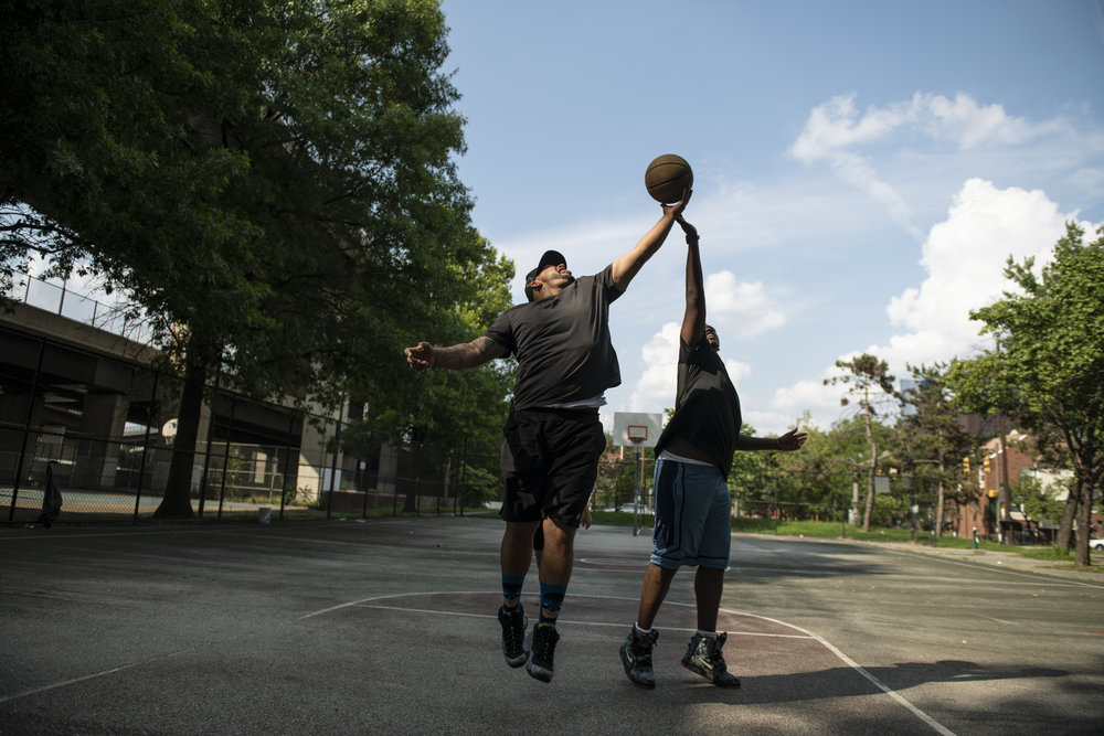 Two adult men with medium and dark skin tones play basketball, their arms are outstretched in a motion that suggests they are literally and figuratively reaching for hope.