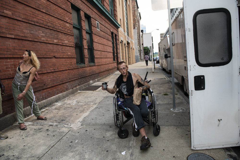 An adult man with light skin tone who uses a wheelchair is pictured on the sidewalk outside a safe needle exchange site. To his left stands an adult woman with medium skin tone and bright blond hair.