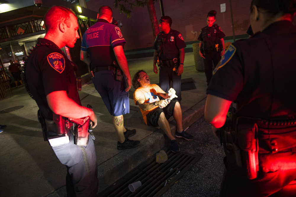 Police officers encircle an adult man with medium skin tone sitting on the pavement. The man is likely overdosing on drugs and his head is violently cocked back in anguish as the red glare of a police light jets across his face.