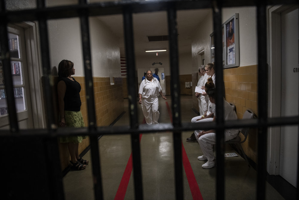 An older person with dark skin tone walks down the hallway of a women's prison.