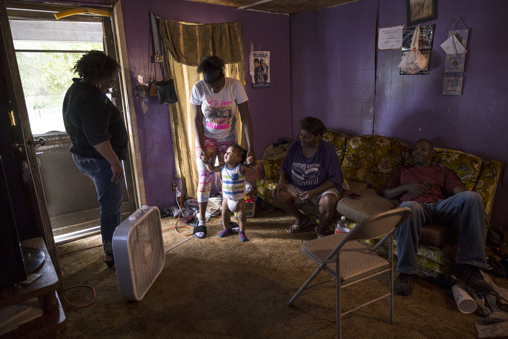 An adult woman with dark skin tone stands in the small purple living room of a family she is helping.