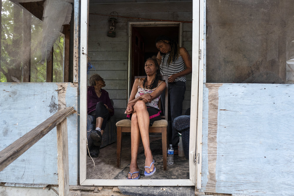 A multigenerational family of women with medium to dark skin tone sits on a porch together braiding hair.