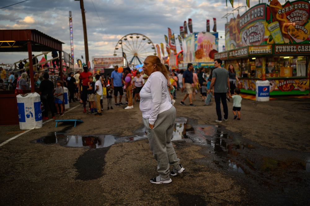 An older person with dark skin tone wearing causal clothing stands in the middle of a bustling fair ground.