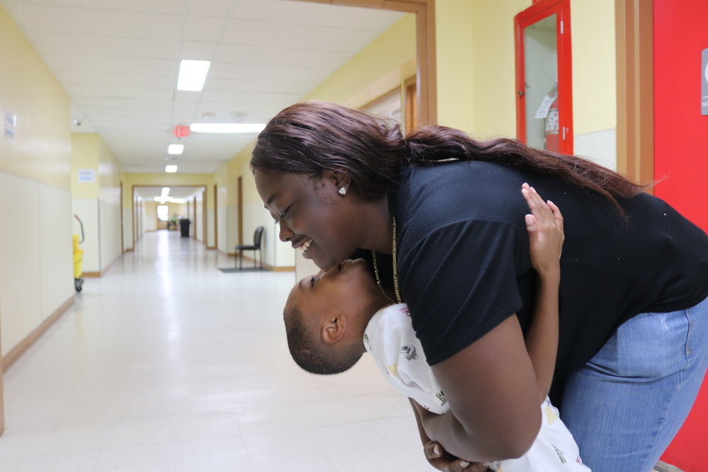 An adult woman with dark skin tone and her young son with medium-dark skin tone are photographed embracing and smiling.