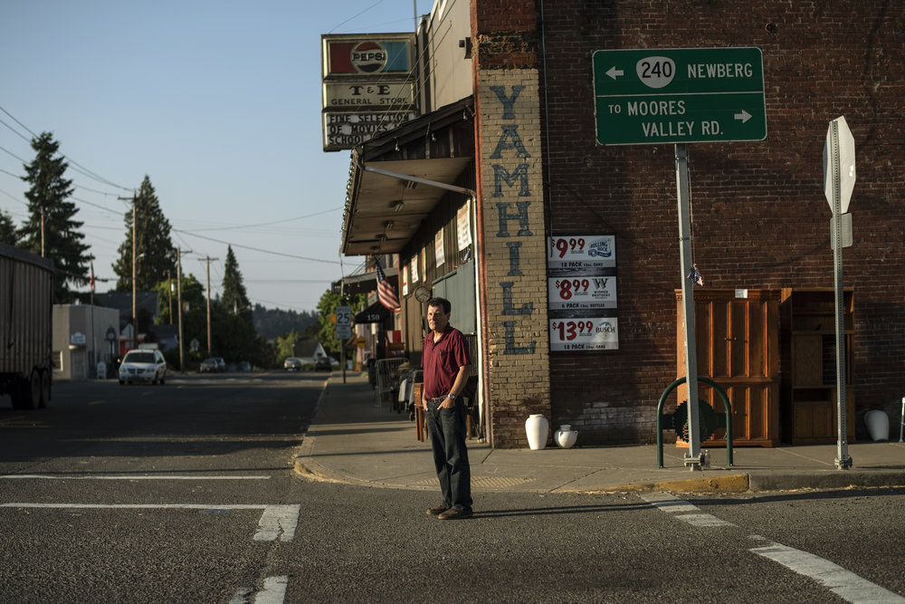 A light skinned adult man wearing a red t-shirt stands somberly in front of a brick general store.