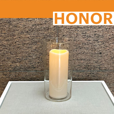 """Lit yahrzeit candle on display with word """"HONOR"""""""